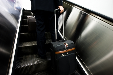 businessmen with suitcase on escalator at the airport. Motion blur.  photo