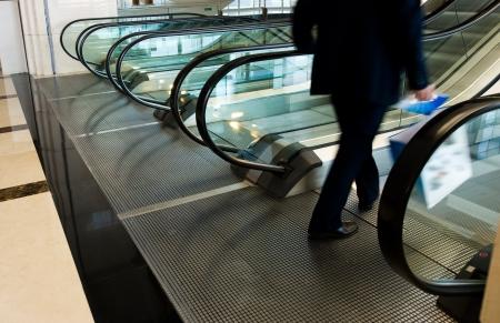 bajando escaleras: hombre vestido con un traje de negocios va hacia abajo en la escalera mecánica.