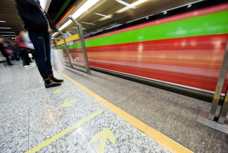 People waiting in subway station with motion blurred train beside.
