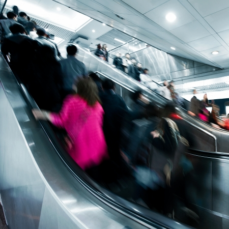 subway station: business people rushing on the escalator in motion blur on the subway station.