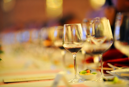 Glasses of red wine in a row on table