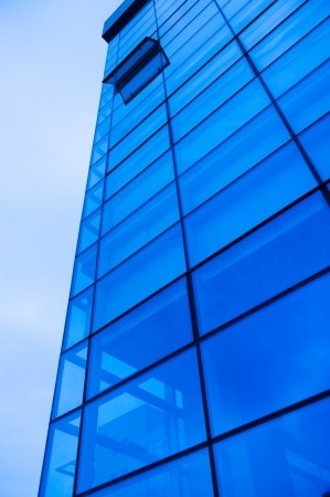 A modern glass fronted building  with the sky and clouds   photo