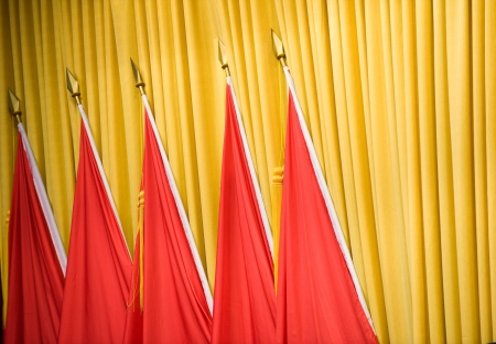 five red flags in front of beige curtain. Stock Photo - 13967418