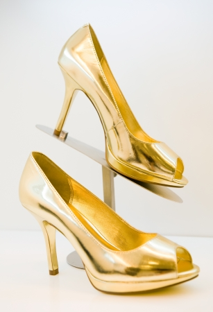 heeled: golden stiletto high heels on white background
