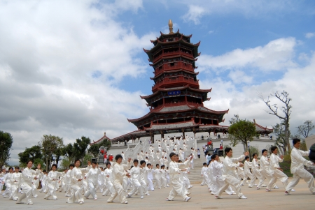 chi: FUJIAN - September 23:  A group of asian people exercising tai chi (a kind of Chinese kung fu) in front of a Chinese traditional tower.  on September 23, 2007 in Fujian, China.