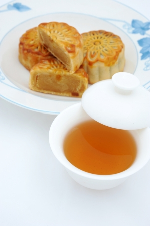 semisweet: Chinese moon cakes and tea  for Chinese mid-autumn festival. The tea is in focus, and cakes are blurred.   Stock Photo
