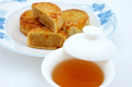 Chinese moon cakes and tea  for Chinese mid-autumn festival. The tea is in focus, and cakes are blurred.   photo