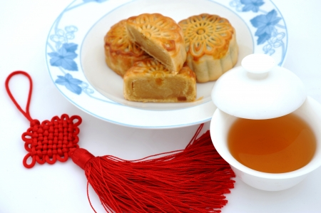 garnished: Chinese moon cake, tea and Chinese knot , for Chinese mid-autumn festival. The tea is in focus, and others are blurred.   Stock Photo