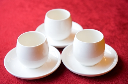 Three tea cups on red cloth background. photo