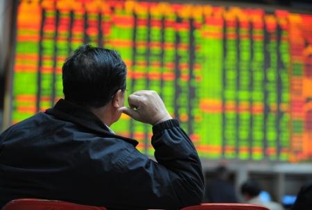 stock index: Asian man watching stock market index.