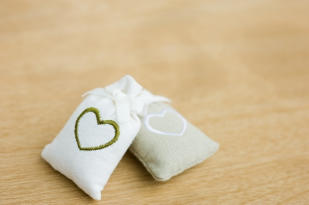 two bags with heart symbol on wooden background.   photo