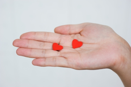 devotions: love concept. holding a red heart in hands.