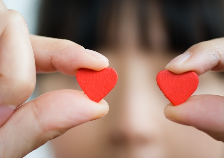 two hearts: love concept. holding a red heart in hands.