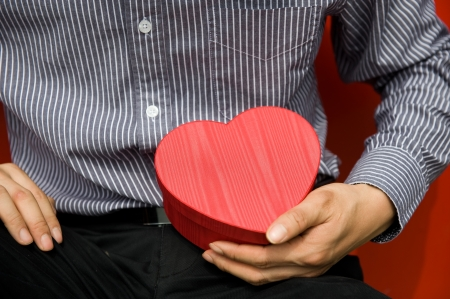 Heart shaped gift box in hands. photo