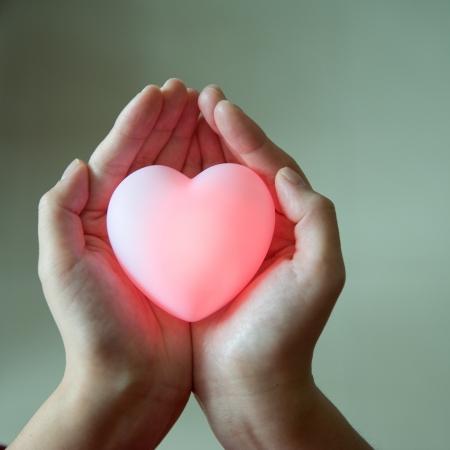 bondad: encanta el concepto. la celebración de un corazón rojo en las manos.