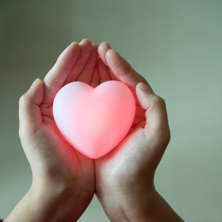 love concept. holding a red heart in hands.  photo