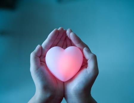 aide à la personne: love concept. tenant un coeur rouge dans les mains.
