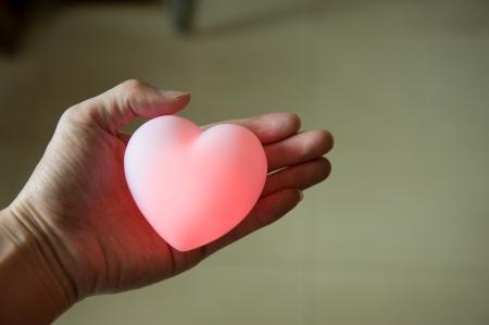 aide à la personne: j'aime concept. tenant un coeur rouge dans les mains.