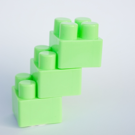 green plastic building blocks on white background  photo