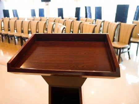 antes de una conferencia, los micrófonos delante de sillas vacías.