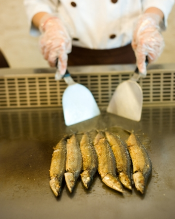 cook griddle: Japanese chef cooking traditional saury teppanyaki on a hot plate.