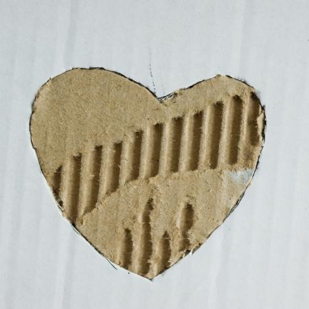 Heart shape hole through paper. photo