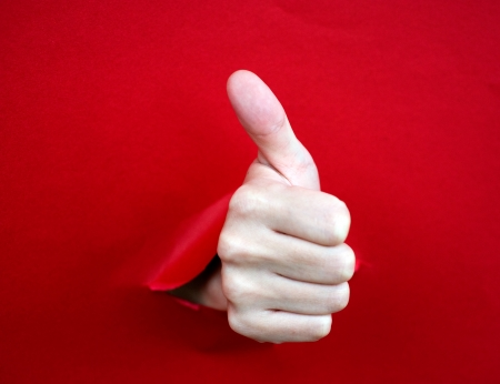 human hand with thumb up, coming out from a broken sheet of paper. photo
