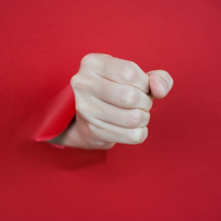 Hand punching through paper isolated on red background  photo