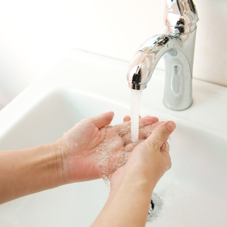 rinse: human hands being washed under stream of pure water from tap