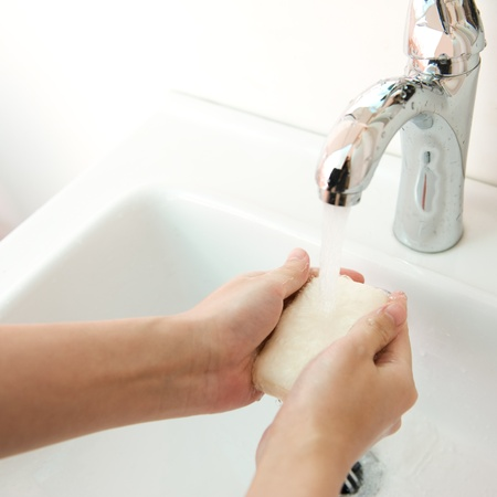 wash basin: Washing hands with soap in the bathroom Stock Photo