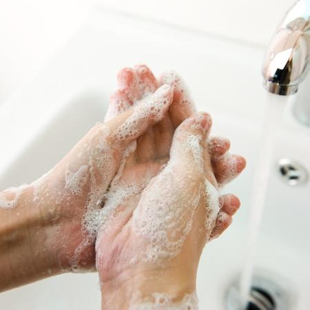 jabon liquido: El lavado de manos con jabón bajo el grifo. Foto de archivo