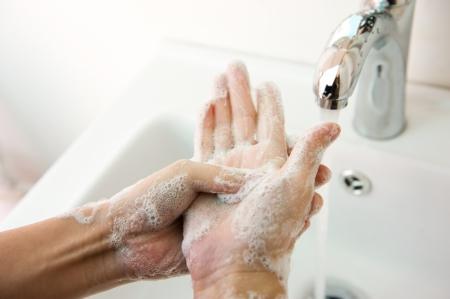 manos: El lavado de manos con jabón bajo el grifo. Foto de archivo