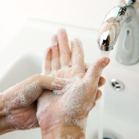 lavarse las manos: El lavado de manos con jab�n bajo el grifo. Foto de archivo