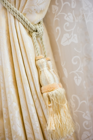A curtain hold back by tassel  photo