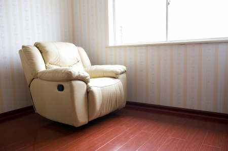 beige leather armchair near the window.  photo