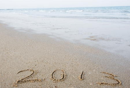 2013 written in sand on beach with sea waves. photo