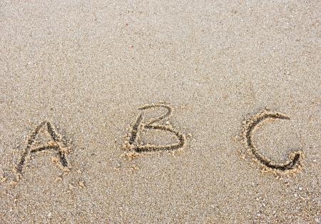 alphabet letters handwritten in sand on beach  photo