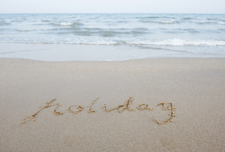 The word holiday written in the sand on a beach.  photo