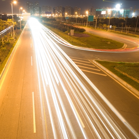 The light trails on the modern building background in urban city of China. photo