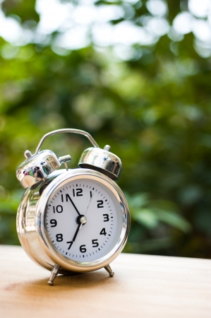 alarm clock: alarm clock on table with green background. Stock Photo
