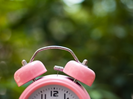 alarm clock on table with green background. photo