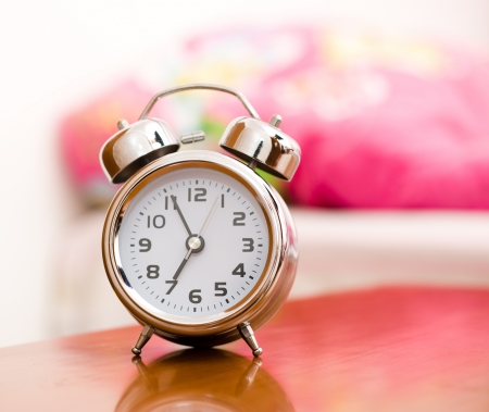 early morning: Alarm clock on night table at bed