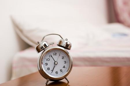 reloj despertador: Alarma en la mesa de noche en la cama