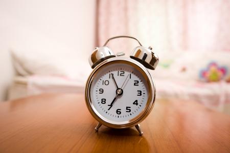 despertador: Alarma en la mesa de noche en la cama