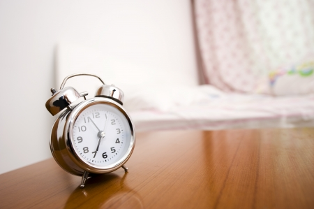 oversleep: Alarm clock on night table at bed