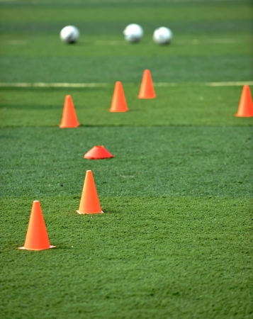 obstruct: footballs and plastic obstacles on the soccer field.  Stock Photo