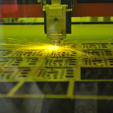 metal processing: Industrial laser cutter with sparks.