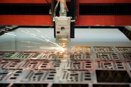 workpiece: Industrial laser cutter with sparks.