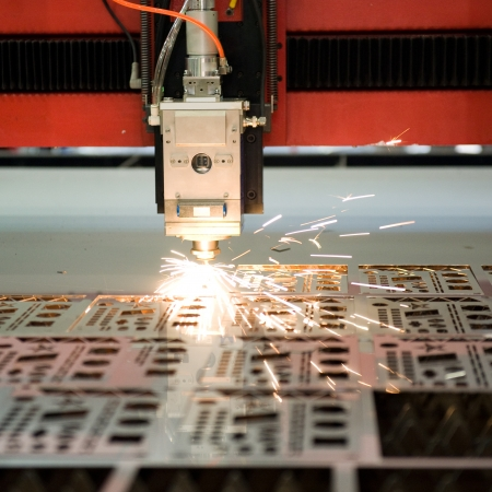 cutter: Industrial laser cutter with sparks.