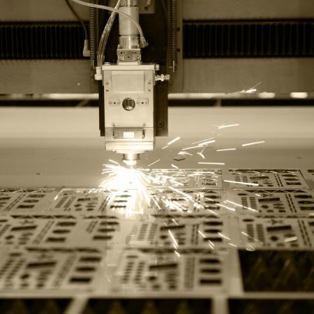 Industriële laser cutter met vonken.